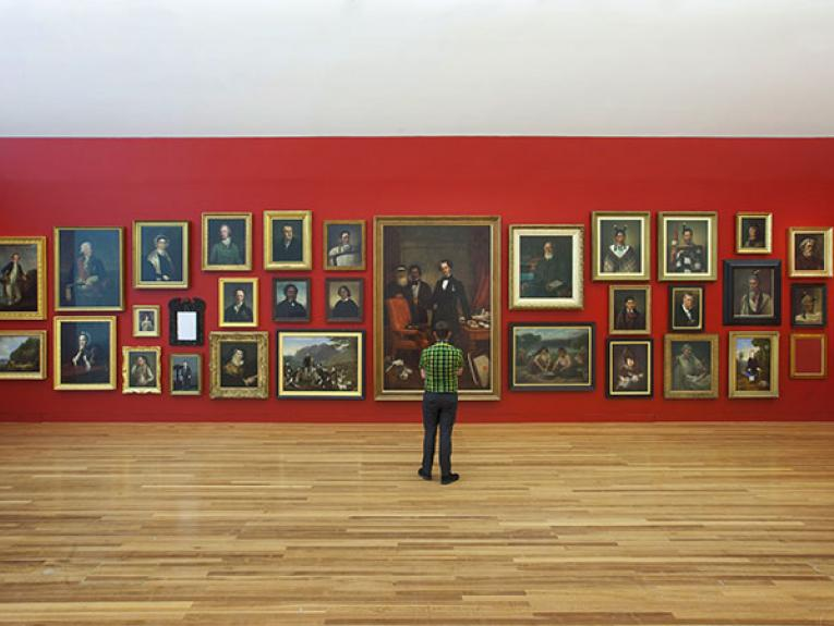 A man stands looking at a red wall featuring paintings hung in the salon style