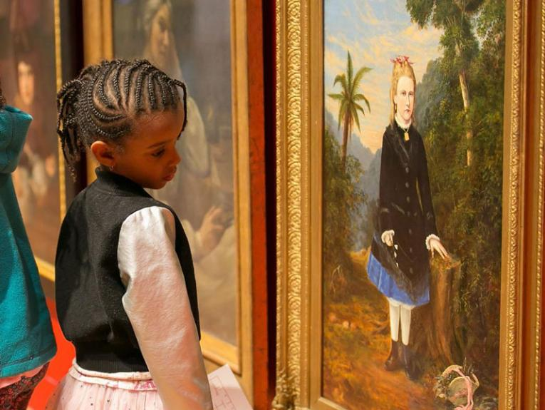 Little girl looks at an oil painting of a child from the 1800s
