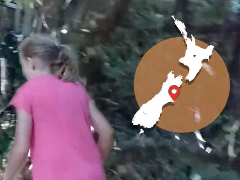 A girl in a pink tshirt is walking off screen and there's a map of New Zealand overlaid on the top right