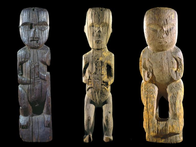Three pou kātua, depictions of persons carved into wooden posts