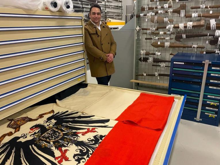 A man in a khaki coat stands against a set of storage drawers. On of the drawers is open and on display in it is an Imperial German flag featuring stripes of equal size in black, white, and red. In the middle is a picture of a large black eagle