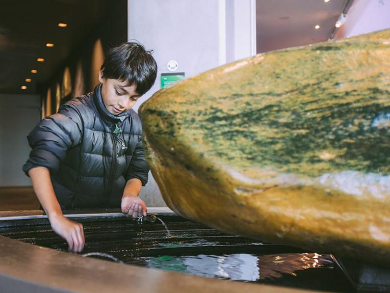 A boy touches a pounamu rock