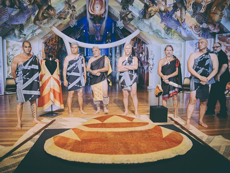 Hawaiian delegates in ceremonial garments standing over the feathered cloak at the powhiri at Te Papa's marae