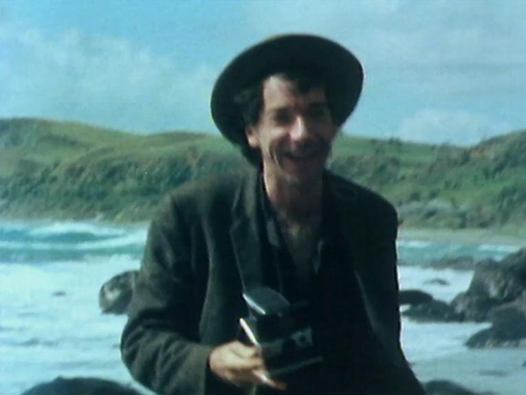 Tony Fomison standing on a beach laughing while holding a camera