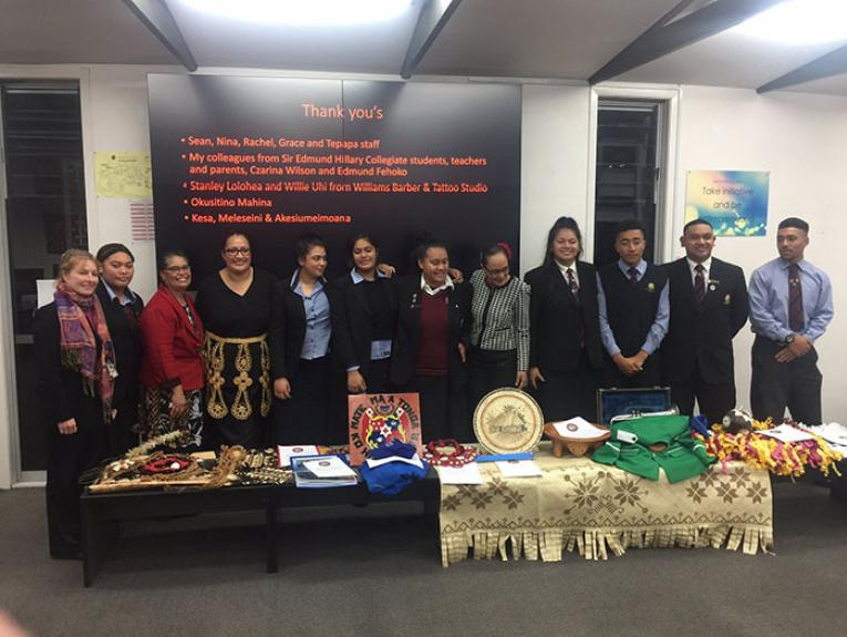 Students pose with their collected objects with a screen behind them saying thank you