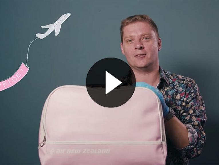Chris Brickell holds a pink Air New Zealand travel bag. An illustration of an aeroplane flies behind him with a pink flag saying 'Pride' behind it