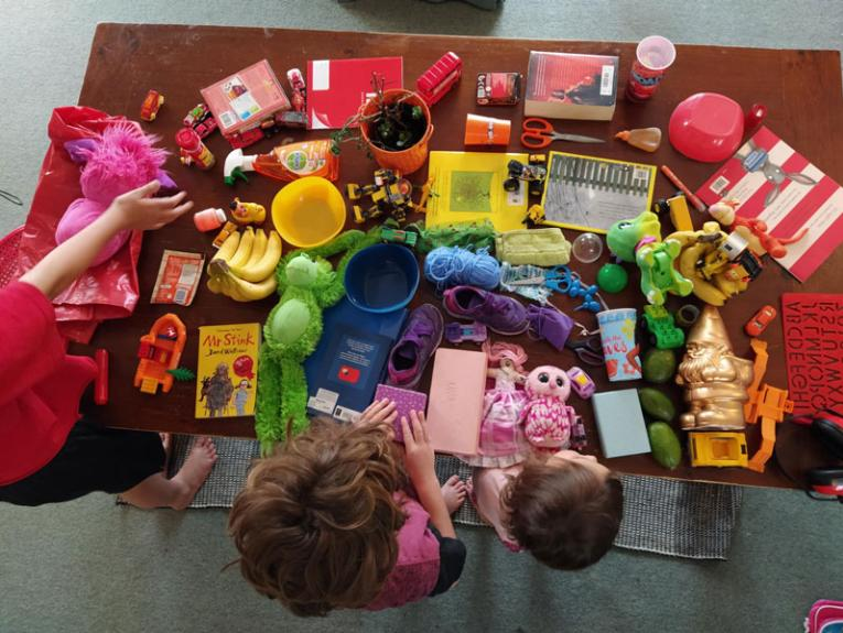 Three kids make a rainbow from toys and other household items
