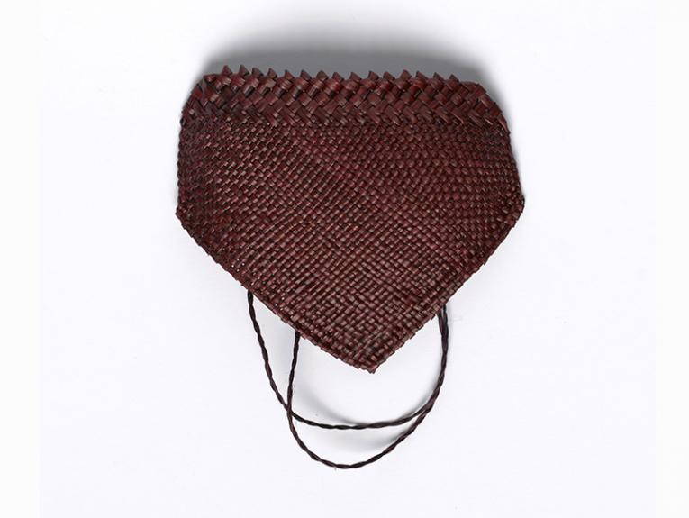 A brown face mask woven with flax on a white background