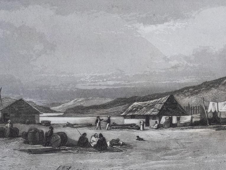 Two buildings on a harbour front, with people sitting about. Many barrels are in the foreground. Washing hangs on the line.