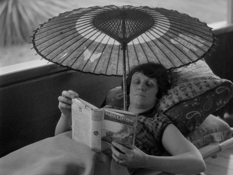 A lady reads inside under a parasol