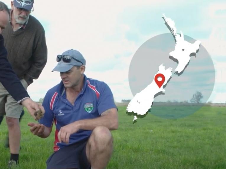 Men looking at something on the grassy ground. There's a map of New Zealand overlaid on the image on the top right-hand side.