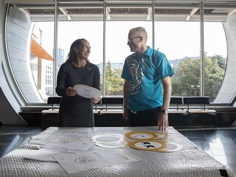 Two people stand in front of a table with an array of safety notices on it