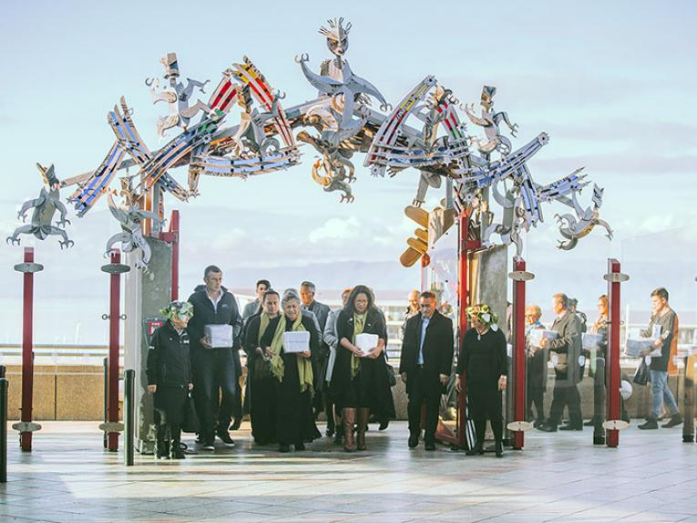 Group of people bring boxes containing the remains through the gates to the marae, with Wellington Harbour in the background