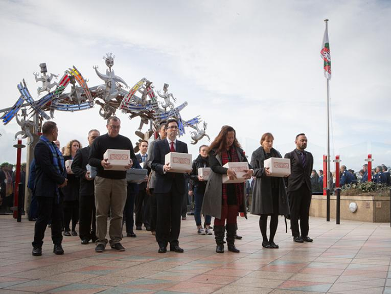 A group of people hold boxes containing Māori and Moriori skeletal remains