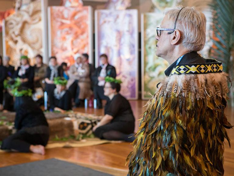A man in a feathered cloak at a repatriation ceremony at Te Papa's marae
