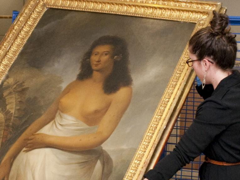 A woman holding a painting wearing blue gloves