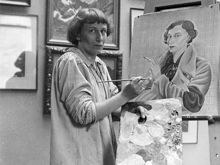 Rita Angus looks towards the photographer in a portrait of her painting herself