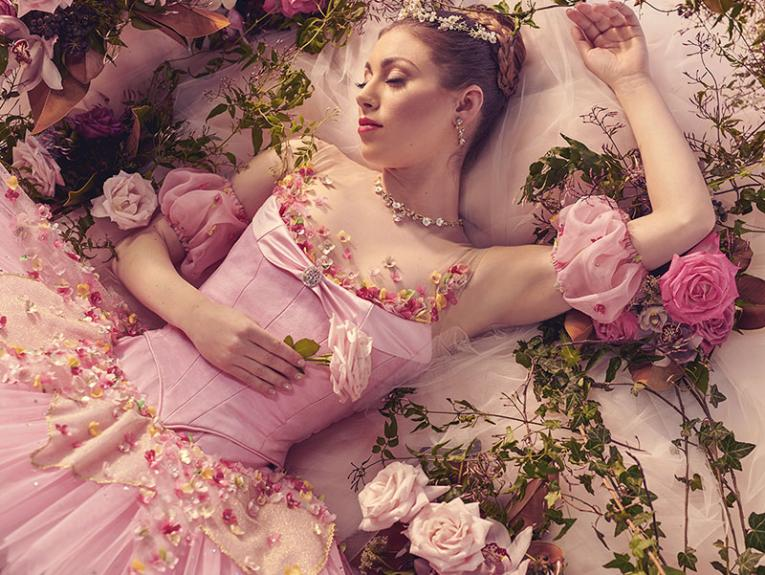 Ballerina in pink sleeping on pink lace surrounded by pink roses
