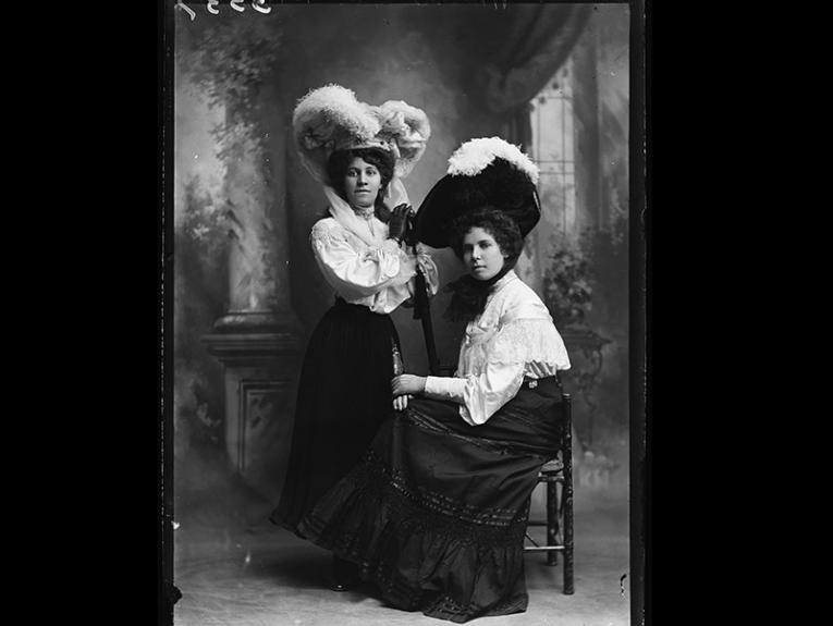 Black and white photo of two women one seated, one standing with enormous hats adorned with large feathers