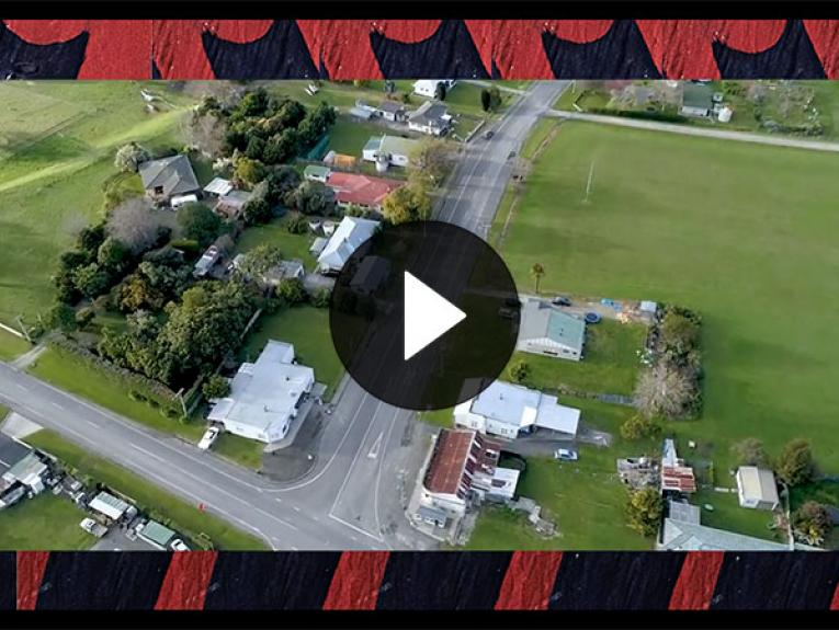 Still from video showing overheard shot of a town, the video footage is frames by carving of a Māori motif