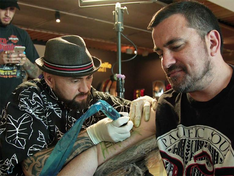 A man receiving a Samoan tatoo in Te Papa