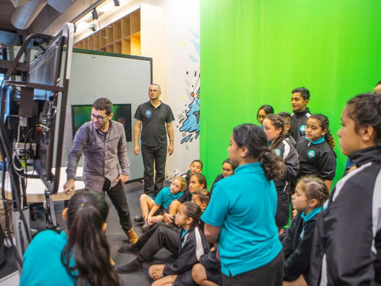 A class taking part in a Hīnātore session by a green-screen