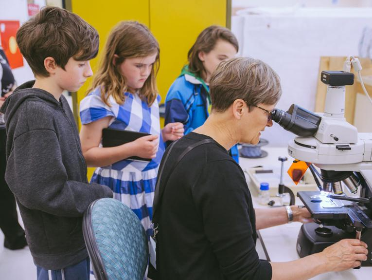 Young school children watch a painiting conservator at work