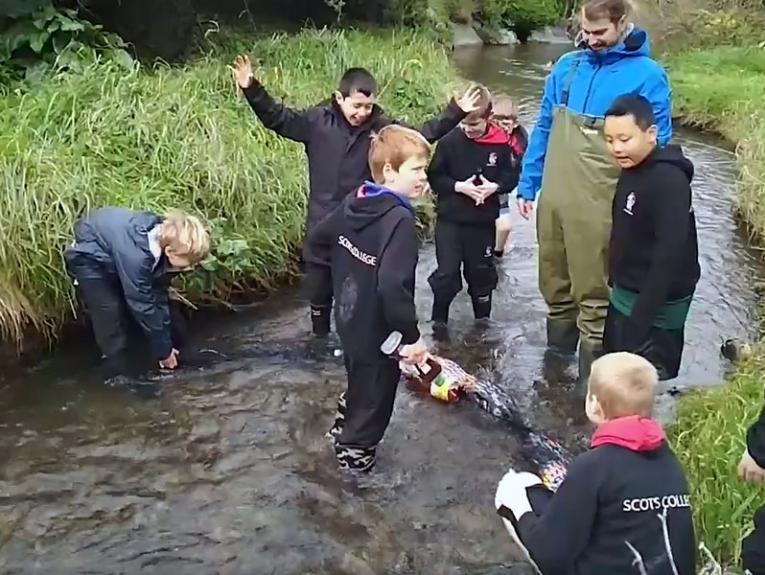 School kids cleaning a river of plastic