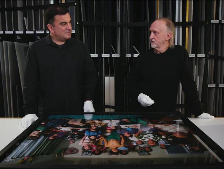 Two men standing in front of a photograph, both wearing white gloves
