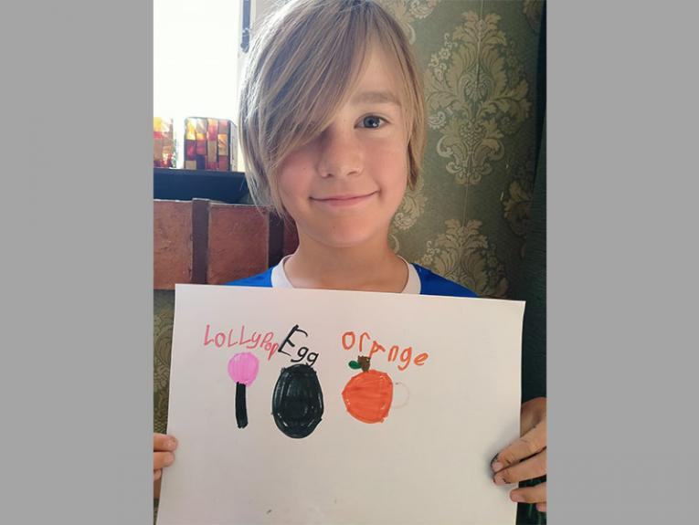Boy holds sheet of paper. On the paper he has drawn a lollipop, and egg, and an orange to represent the letters of his name