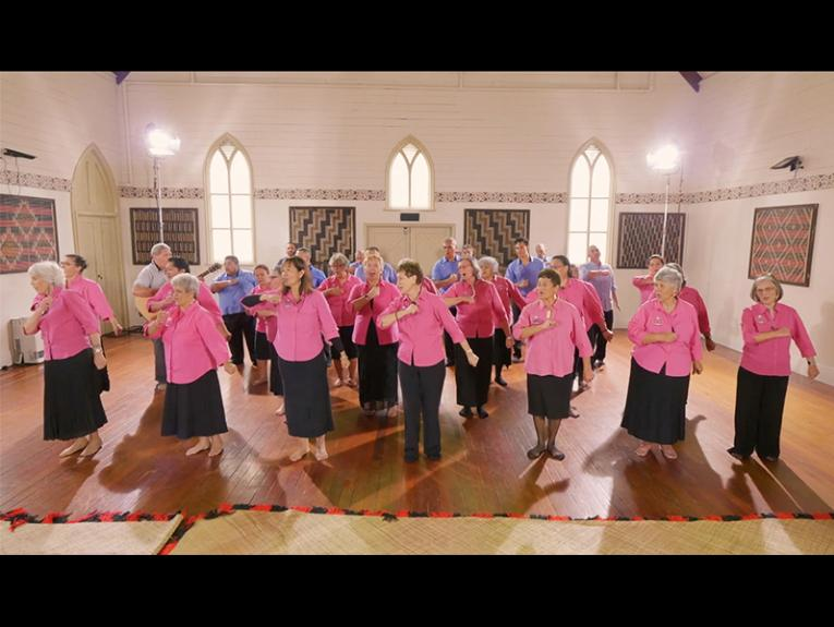 A group of older people wearing pink shirts and blue shirts dancing in formation inside a church hall