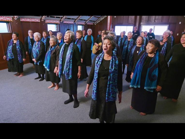 Several women in a room wearing black shirts with blue and turquoise scarves singing in unison