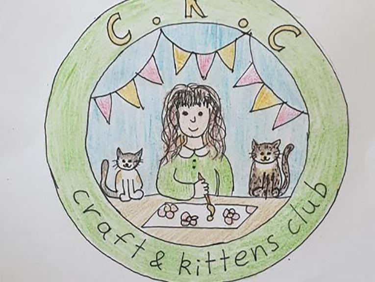 Drawing of a badge with a green circle containing the words 'Craft and Kittens Club'. Inside the circle is a scene of a woman, wearing green, painting, flanked by two kittens. Red and yellow bunting flies above her