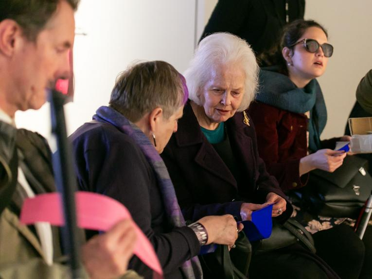 Two women feel and discuss a long, blue strip of bright paint. Beside them, a man holds a pink strip