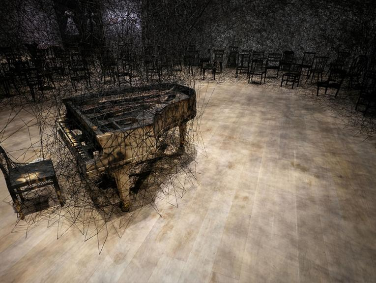 Burnt piano and chair stand in a room. Behind them are an array of chairs connected to each other and the stairs via black wool