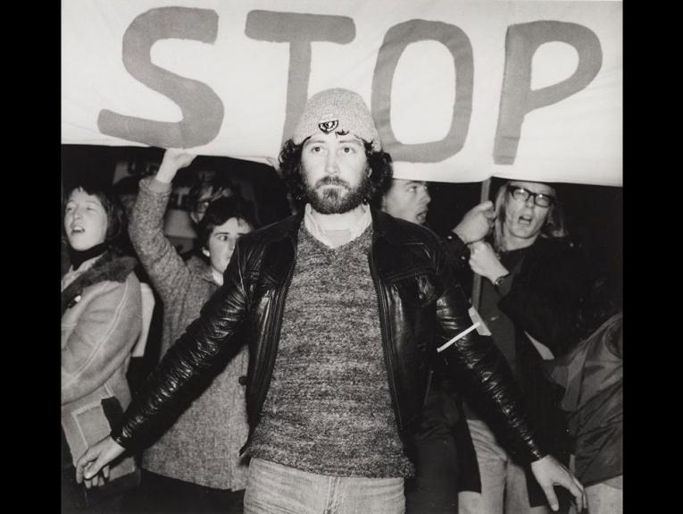 A man stands in front of a sign which says 'stop'