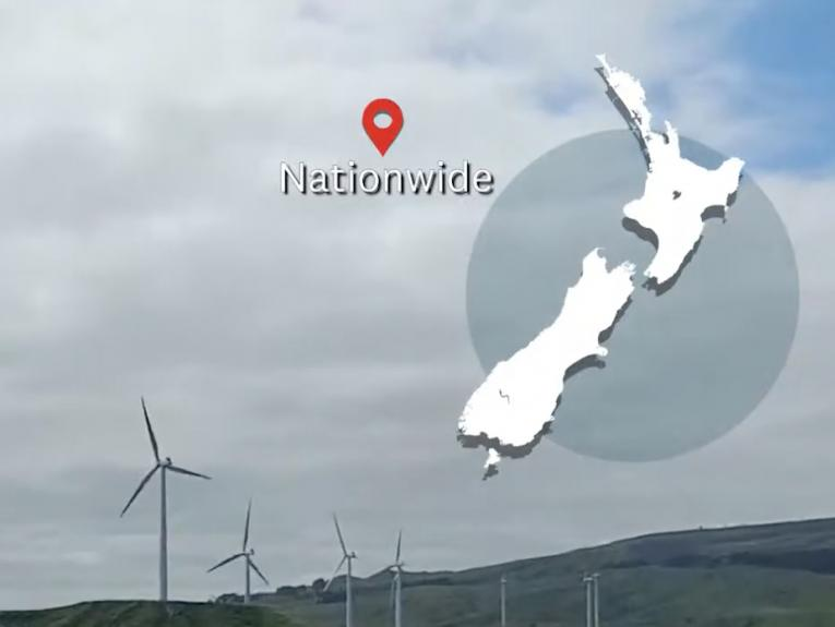 A windfarm on a grey day with a map of New Zealand overlaid in the top right-hand corner