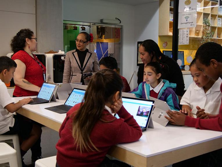 Students and teachers work at a desk full of computers