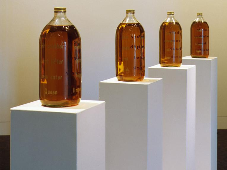 Four large bottles containing beer stand on four plinths