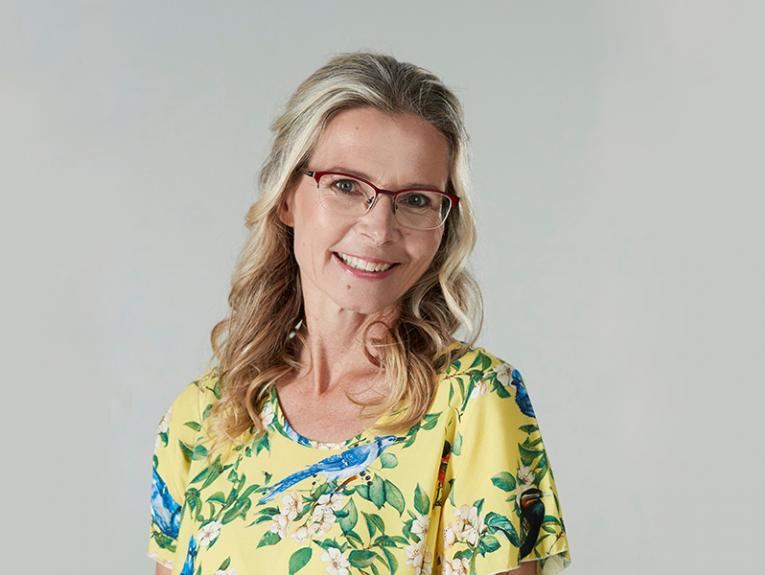 Woman with blond hair and glasses in a yellow floral top in front of a grey background