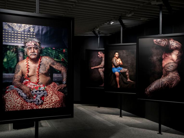 Inside an exhibition, large photographs of tattooed men hang on the walls