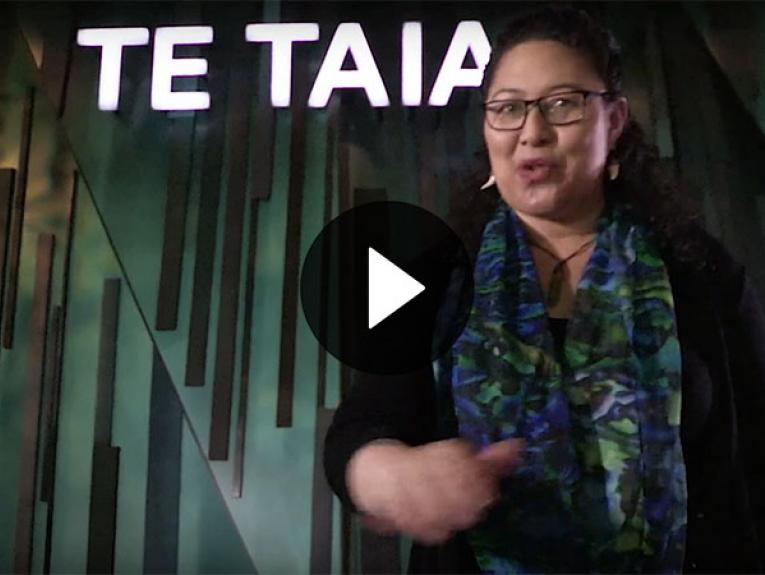 Screenshot of video. A woman stands at the entrance to Te Taiao | Nature talking to the camera