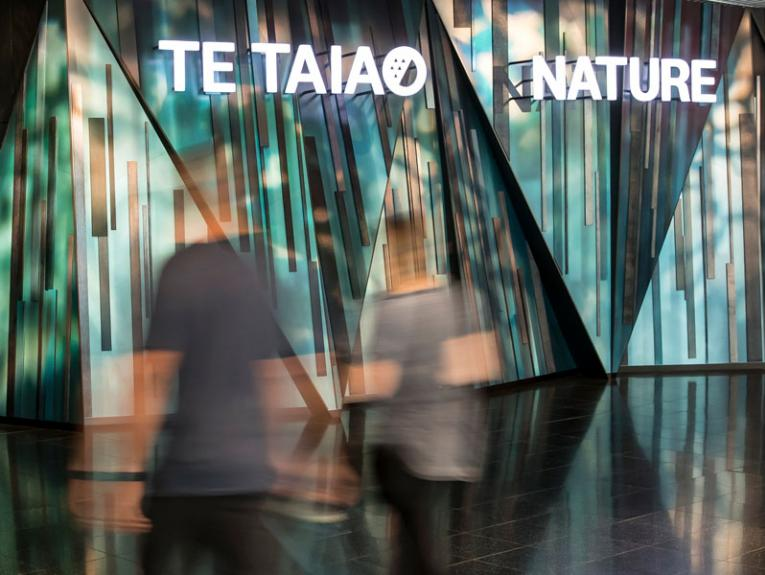 Visitors walking through the entrance of the Te Taiao | Nature exhibition