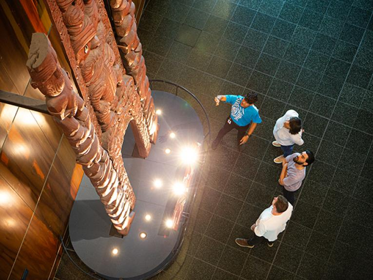 Four people standing in front of a wooden carving in a large space