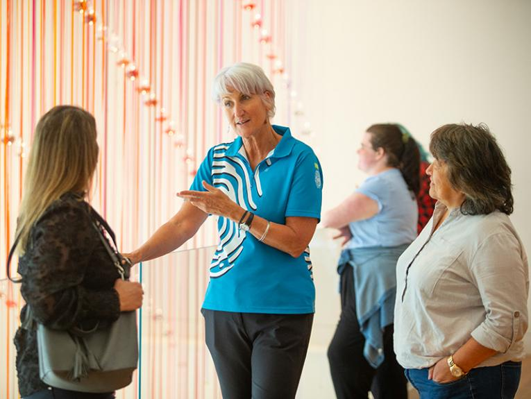 People standing in front of a hanging artwork with one woman explaining what it's about
