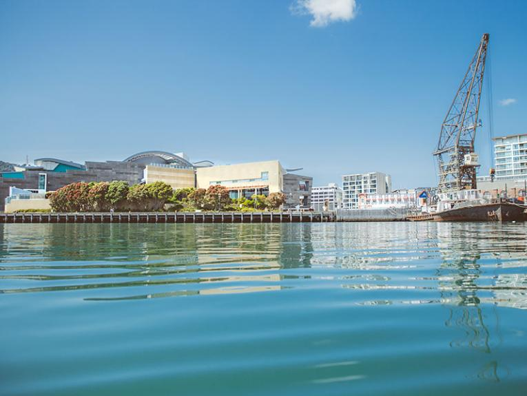 Low shot of Te Papa from the harbour, which dominates the bottom half of the image, with a boat on the right-hand side