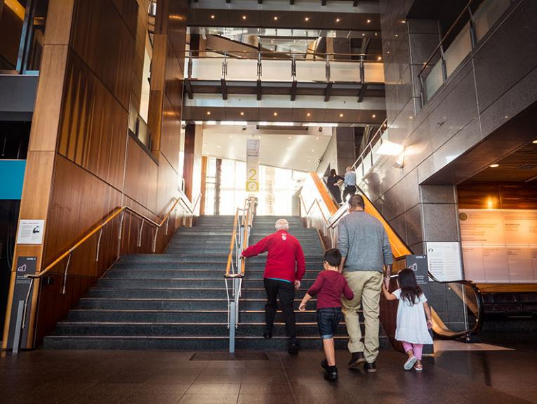 A Te Papa Host guided a man and two small children up the stairs to the main foyer of Te Papa