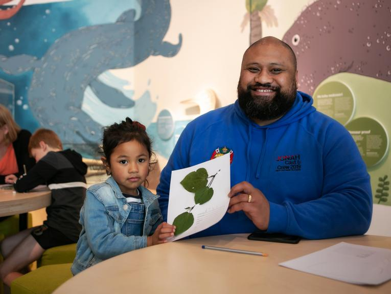 A photo of a man and a child holding up a piece of paper with leaves glued on it