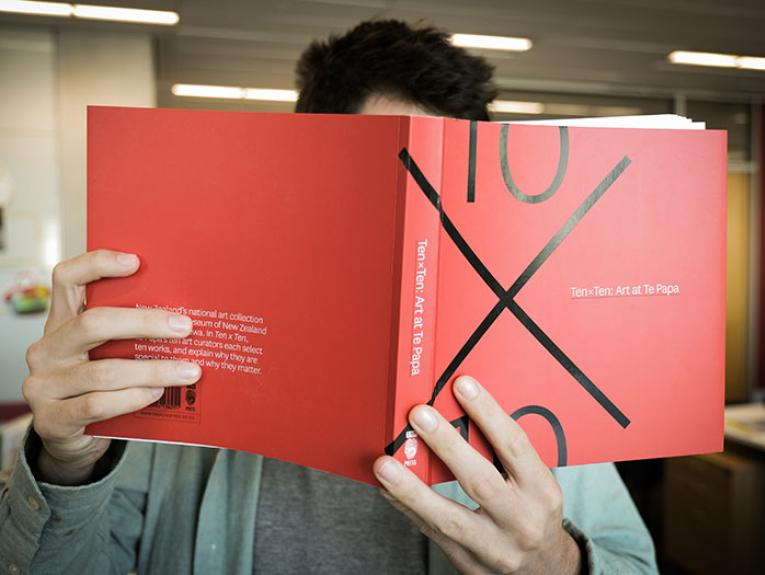 Man holds a copy of the book up