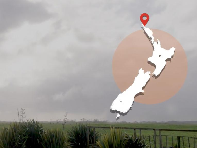 Grey sky over farmland. There's a map of New Zealand overlaid on the image on the top right-hand side.